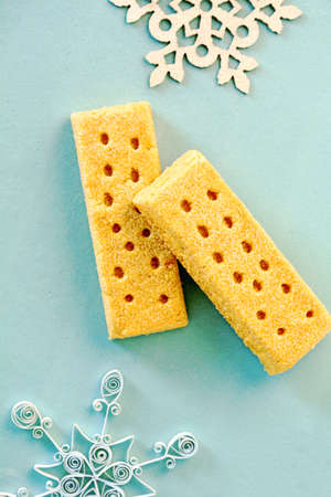 All butter shortbread fingers on aqua background in vertical format in flat lay format.