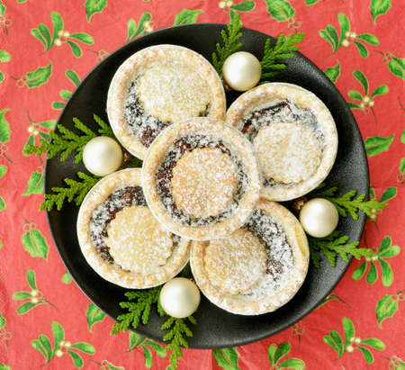 Traditional mince tarts on black plate with cedar and golden balls on festive background in flat lay.