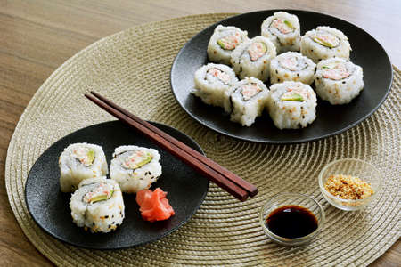Fresh made California sushi rolls on black plates in horizontal format.  Red ginger slices, sesame seeds and soy sauce condiments.