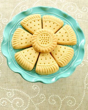All butter shortbread biscuits on aqua cakestand with linen background in vertical format in flat lay format.