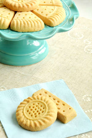 All butter shortbread biscuits on aqua cakestand with linen background in vertical format.