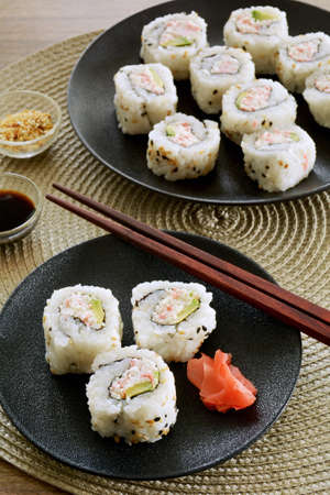 Fresh made California sushi rolls on black plates in vertical format.  Red ginger slices, sesame seeds and soy sauce condiments.