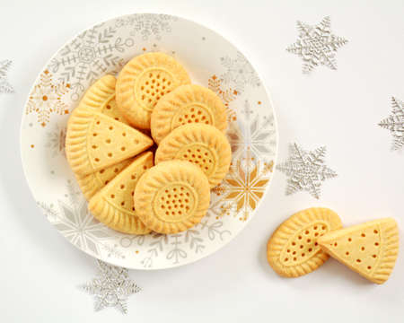 All butter shortbread biscuits on white plate with decorative snowflakes in flat lay format.