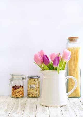 Pink and purple tulips in vintage white jug on rustic wood board in vertical format with room for your text.