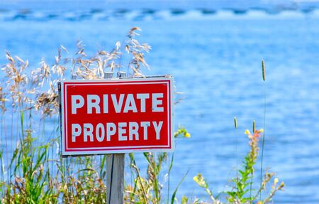 property: White on red private property sign by the ocean. Stock Photo