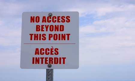 English-French bilingual sign, red on white against a cloudy sky: No access beyond this point-Acces interdit.