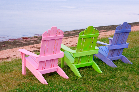three objects: Three wooden lawn chairs, pink, green and blue on grass by the ocean.