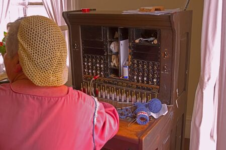 cable knit: Picture of an old telephone switch board with a female operator dressed in vintage clothing. Stock Photo