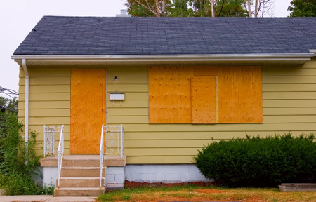 A house in good condition with the door and windows boarded up with plywood.