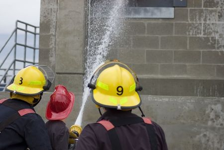 bombero de rojo: Un ni�o peque�o tratando de alcanzar el objetivo con una manguera de agua entrenado por dos bomberos.  Foto de archivo