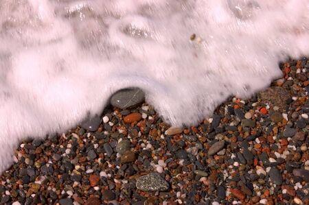 diagonally: Blurred white water foam flowing diagonally over beach pebbles.