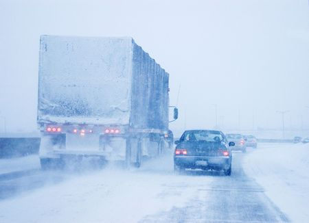 tire: Transport truck and passenger car in a heavy snow storm.