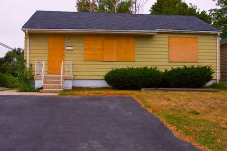 plywood: A house in good condition with the door and windows boarded up with plywood; deserted drive way visible.  Stock Photo