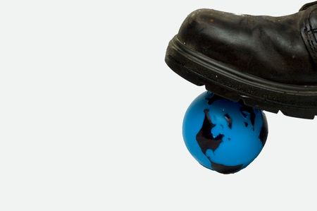 stepping: Concept picture with a black boot stepping on a blue plastic Earth globe.