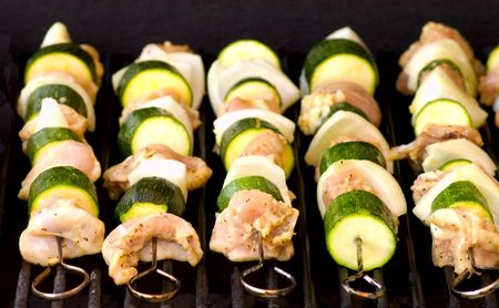 Five stainless steel sqewers with chicken meat, onions and zucchini on the grill.