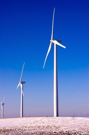 two and two thirds: Vertical shot of three white wind mills shot against a clear dark blue sky in winter. Stock Photo