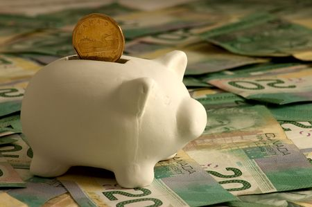 Small white piggy bank sitting on a layer of Canadian twenties bills with a dollar coin (loonie) dropping inside.