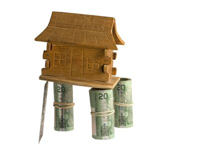 canadian cash: House on three money stilts, the fourth stilt is a credit card. High risk mortgage concept, isolated on white, Canadian cash. Stock Photo