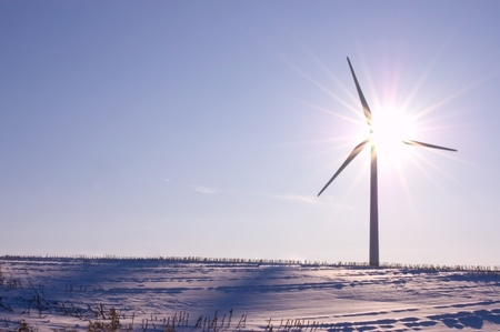 rule of thirds: Wind turbine shot against the sun on the clear blue winter day. Concept picture for renewable energy; rule of thirds, closed aperture. Stock Photo