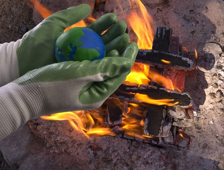 Hands with green gloves hold the Earth glove above a strong fire. Concep picture for the global environmental movement. photo