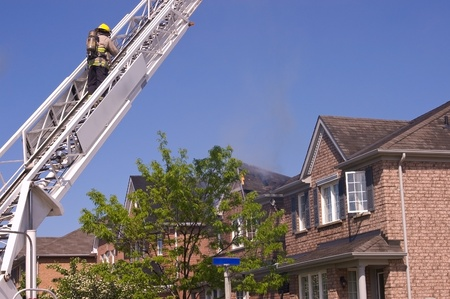 damaged roof: Firefighter wearing a self contained breathing apparatus on an engine ladder surveyes an extinguised fire that damaged a roof top. Editorial