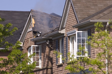 damaged roof: Fire damaged smoldering roof of a non descript brick house. Editorial