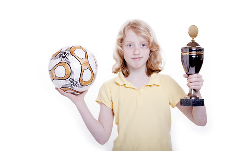 Small girl with a football and the cup in the hand Stock Photo