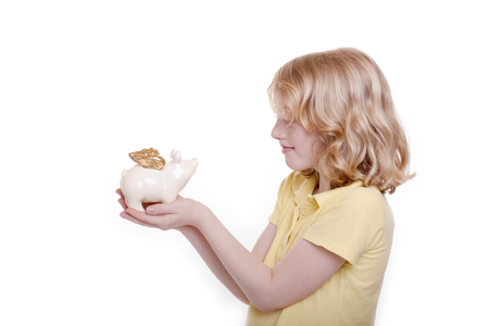Small girl holds piggy bank in the hand