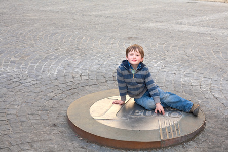 A child sits on a big eurocoin Stock Photo