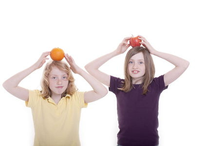 Two girls play with the fruit