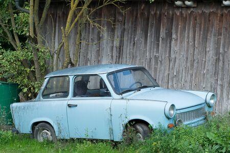 Altes DDR-Auto aus Osteuropa steht auf der grünen Wiese, blaues Oldtimer-Auto Standard-Bild