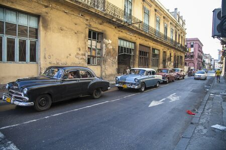 Havana, Cuba - 20 January 2013: The streets of Havana, very old American cars on the streets and horse-drawn coaches with tourists. Editorial