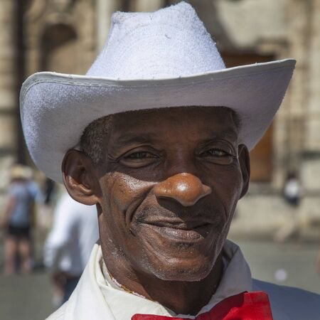 Havana, Cuba - 24 January 2013: Portraits of cuban people in traditional dresses. An elderly cuban man in a white suit and a red bow tie.