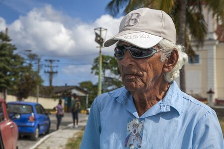 Havana, Cuba - 12 January 2013: A view of the streets of the city with cuban people. A portrait of the old man in baseball cap and sunglasses. Editorial