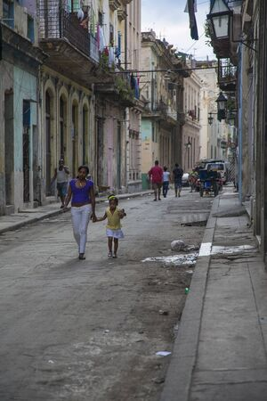 Havana, Cuba - 21 January 2013: A view of the streets of the city with cuban people. A woman with the child goes out on the street. Éditoriale