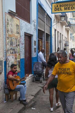 La Havane, Cuba - 21 janvier 2013 : une vue sur les rues de la ville avec des cubains. Un musicien de rue joue de la guitare. Éditoriale