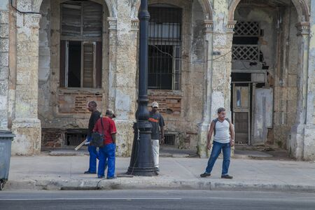 Havana, Cuba - 22 January 2013: A view of the streets of the city with cuban people. Four men are waiting for the bus. Editorial