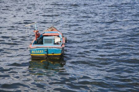 Havana, Cuba - 22 January 2013: An old fishing boat in the middle of the sea. Sea views seen from the coast.
