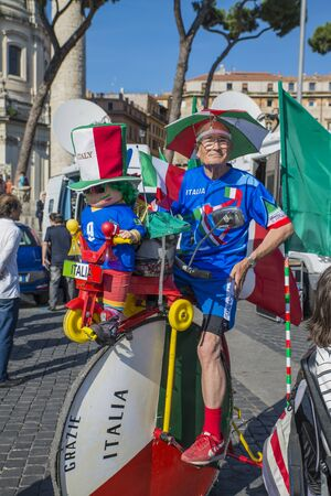 Rome - June 20, 2014 : An Italian soccer fan tifoso rides on a bicycle. He driving with national flag of Italy.