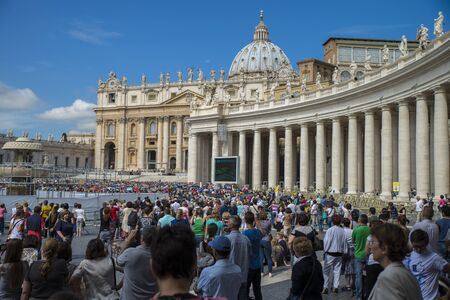 Vatican - June 18, 2014 : Pilgrims come to visit St. Peter's Square in Vatican. Pilgrims in the foreground and a Pope Francis stands on the podium.
