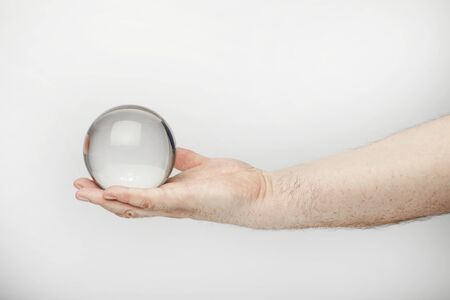 Male hand holds fortune teller ball or crystal ball, isolated  on the white background. 版權商用圖片
