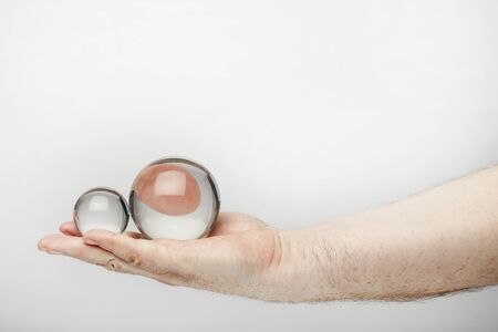 Male hand holds two fortune teller ball or crystal ball, isolated  on the white background. 版權商用圖片