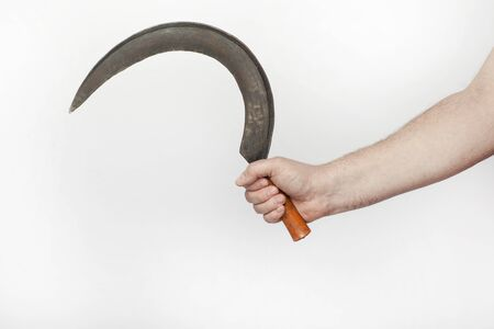 Male hand holds  a old sickle, isolated  on the white background.