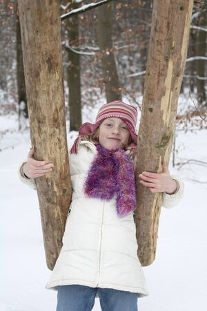 A strong girl holding a tree trunk. Wintry landscape in the forest.