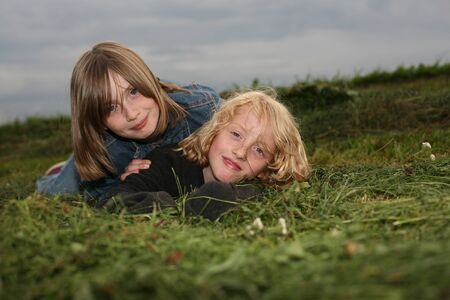 Two girls lying on the meadow.  Dreamlike childhood in the countryside.