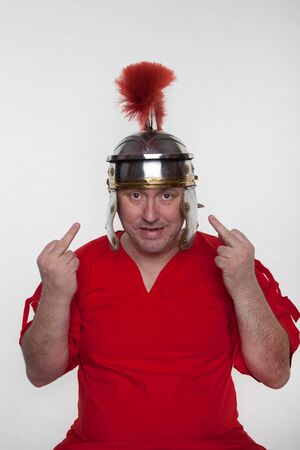 A roman soldier shows fuck with middle finger on the white background.