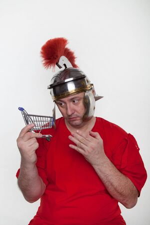 A roman soldier with mini shopping cart on the white background.