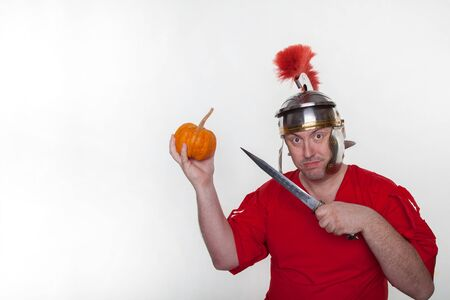 A roman soldier with a pumpkin and dagger on the white background.