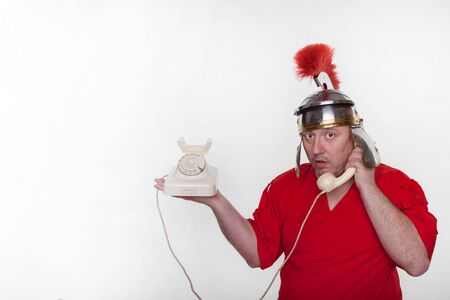 A roman soldier is on the phone on the white background.