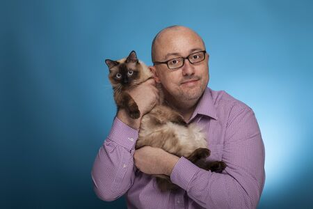 A businessman in a piked shirt holds  a birman cat in the hand,  on the blue background.